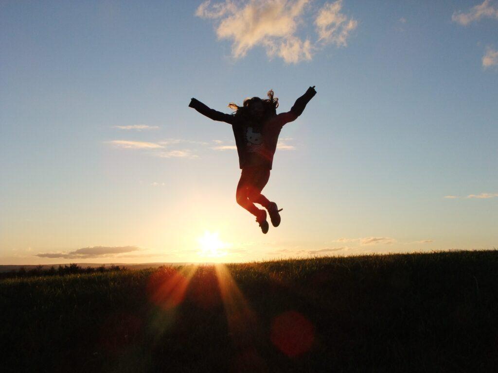 A woman jumps in the air while the sun sets behind a dark horizon.